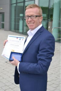 Photograph of Audiologist Christopher Cartwright holding diploma infront of building