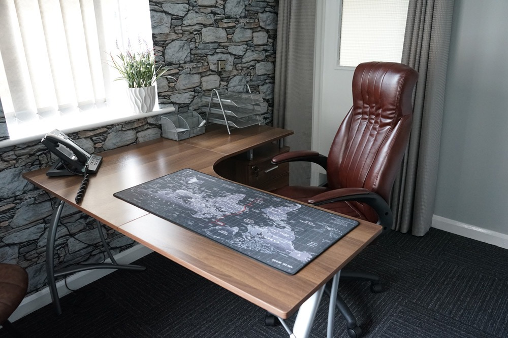 Desk with world map mouse pad and brown leather chair in occupational health clinic