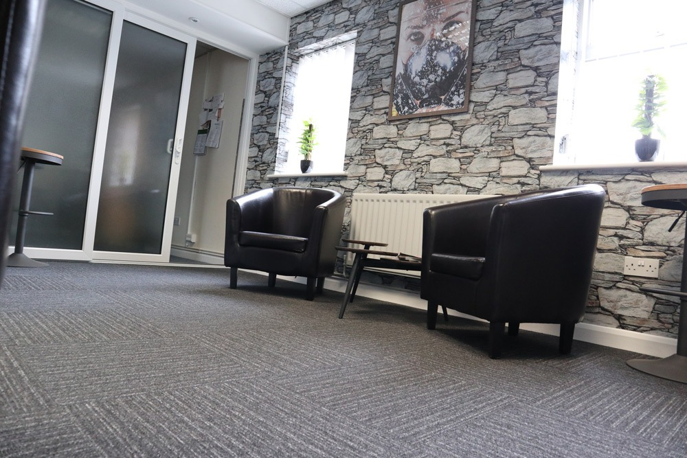 Occupational Health Waiting Area with small black seats and coffee table
