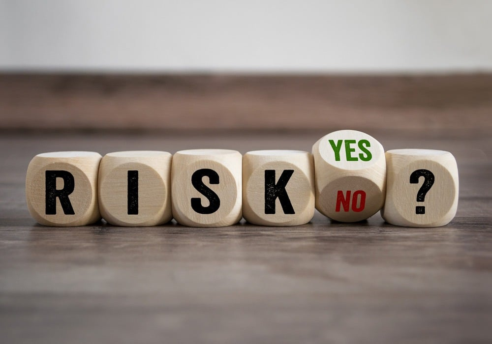 Adobe Stock image of dice spelling out Risk? Yes No on wooden table